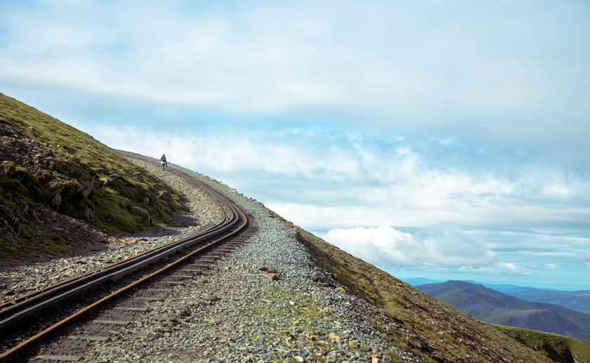 Railway tracks at the top of Snowdon with a lone climber and clouds in the background.