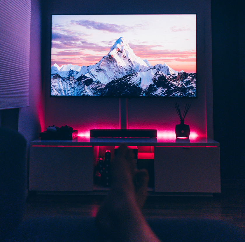 A dark room with a mountain on the tv screen and someone's feet in the foreground crossed