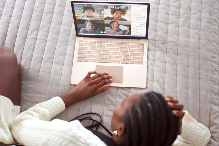 Woman laying on her white bed video calling friends from her laptop.