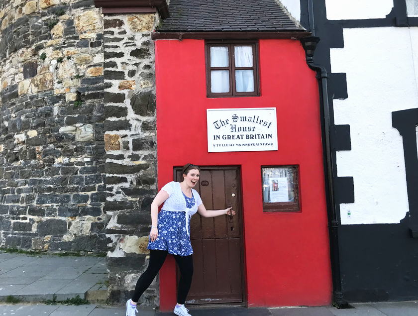 Mel stepping into the smallest house in Britain - a tiny bright red terrace house on the quayside of Conwy.