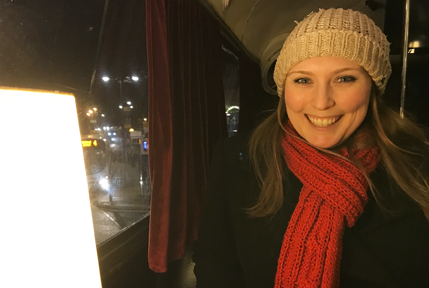 Mel sat on a dark bus at night smiling next to a glowing light wearing a red scarf and wooly hat