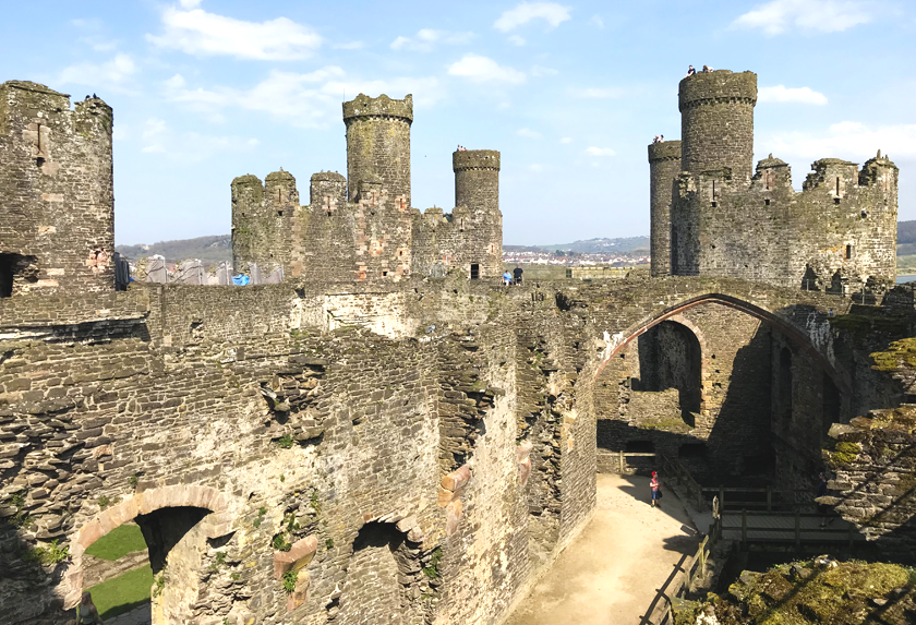 Inside Conwy castle, stone walls and sand paths.