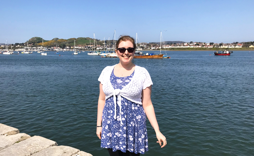 Mel standing by Conwy quayside with the marina in the background and boats sailing.
