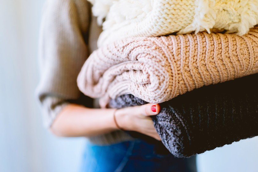 Person's hands holding a stack of neutral coloured woolly jumpers