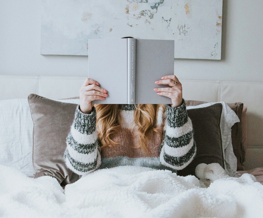 Woman wearing a stripped woolly jumper, sat in her bed with a grey book held up over her face