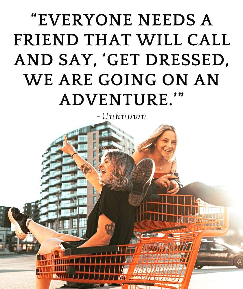 Two girl friends laughing riding in a shopping trolley goofing around