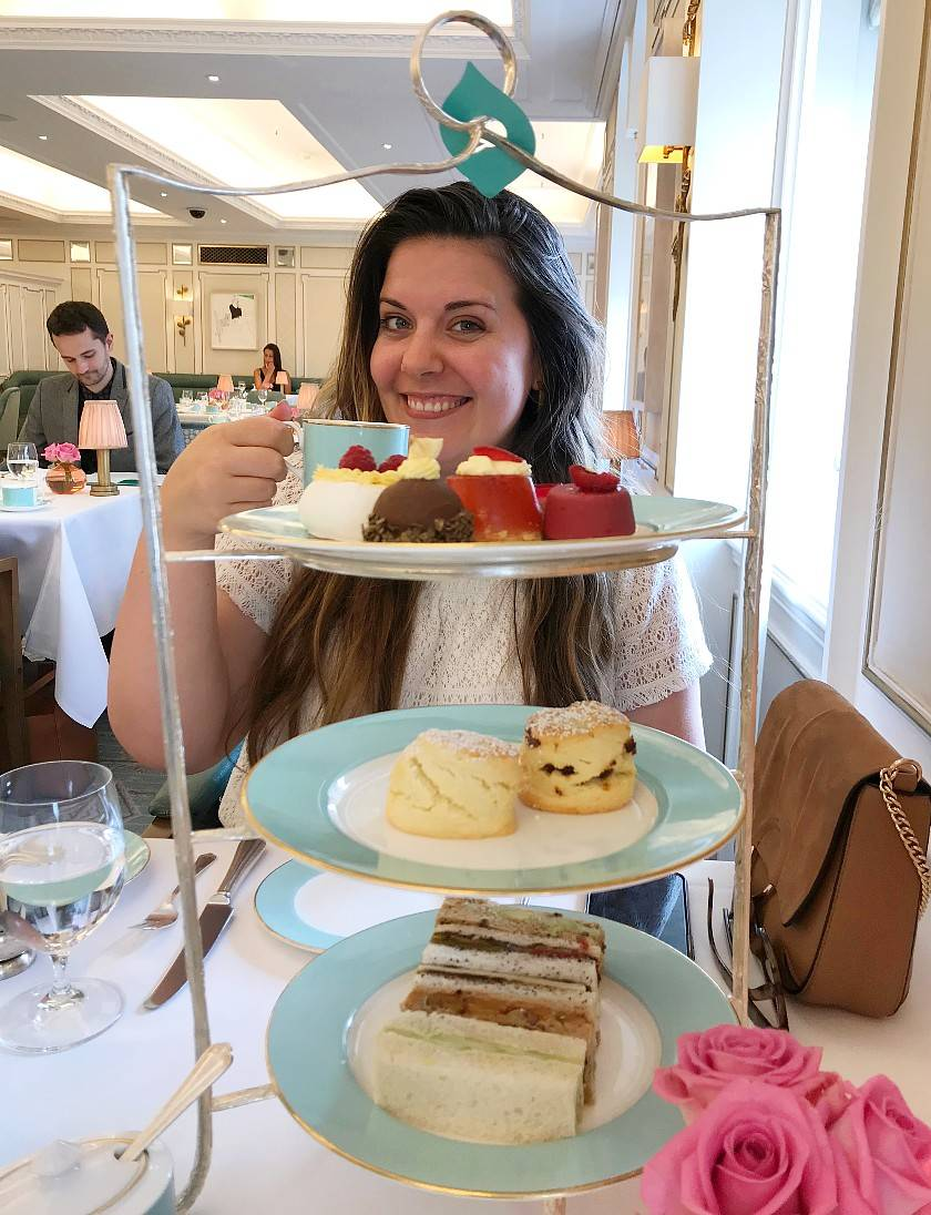 Mel's friend Tami sat behind her vegan afternoon caddy holding up a cup on tea in her hand