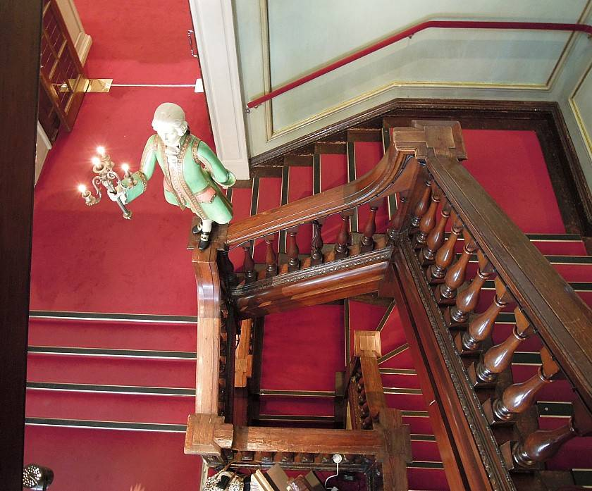 Looking down the wooden staircase in fortnum and mason with red carpet and wooden statue light fixture
