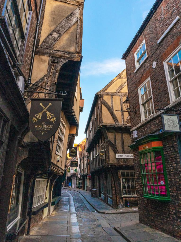Medieval main street in York, UK with brown facades, windows and signs which looks like Diagon Alley from the Harry Potter film series
