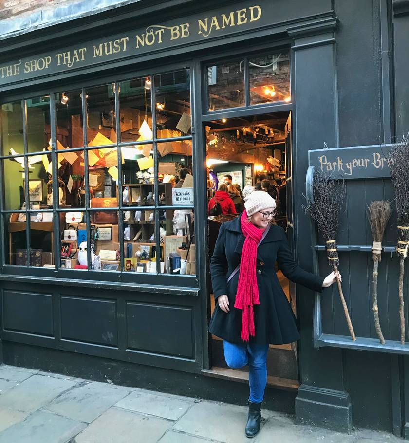 Mel stepping out of the 'Shop that must not be named' grabbing a broom from outside down The Shambles in York