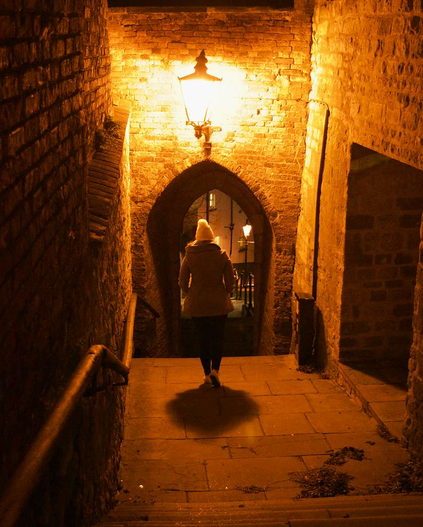 Mel walking through a spooky medieval archway at night with yellow light from the street lantern