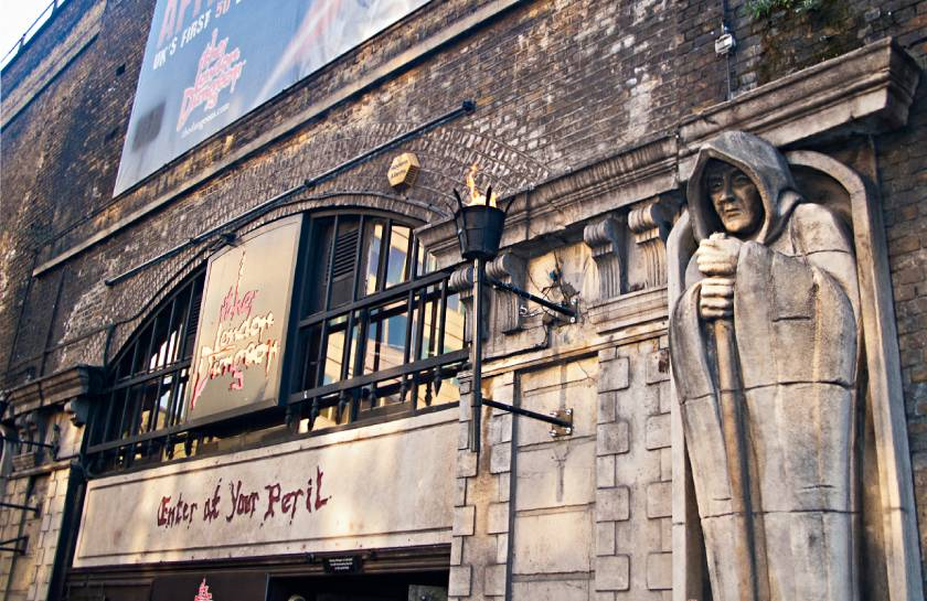 Outside of London Dungeon with formidable stone statue and black railings