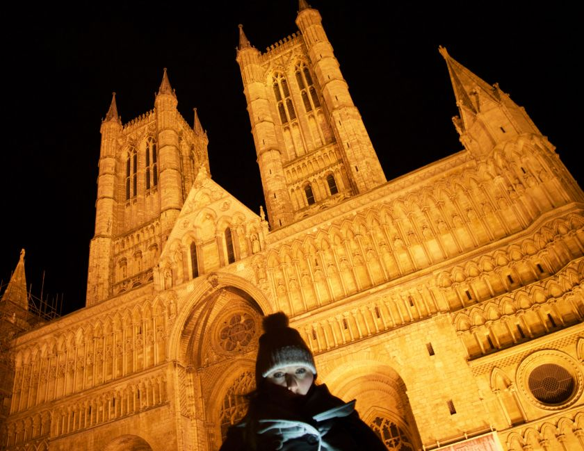 Lincoln Cathedral lit up at night on the Lincoln ghost walk with Mel in the foreground under a shadow