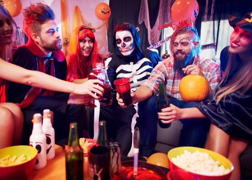 People dressed up at a halloween party saying cheers