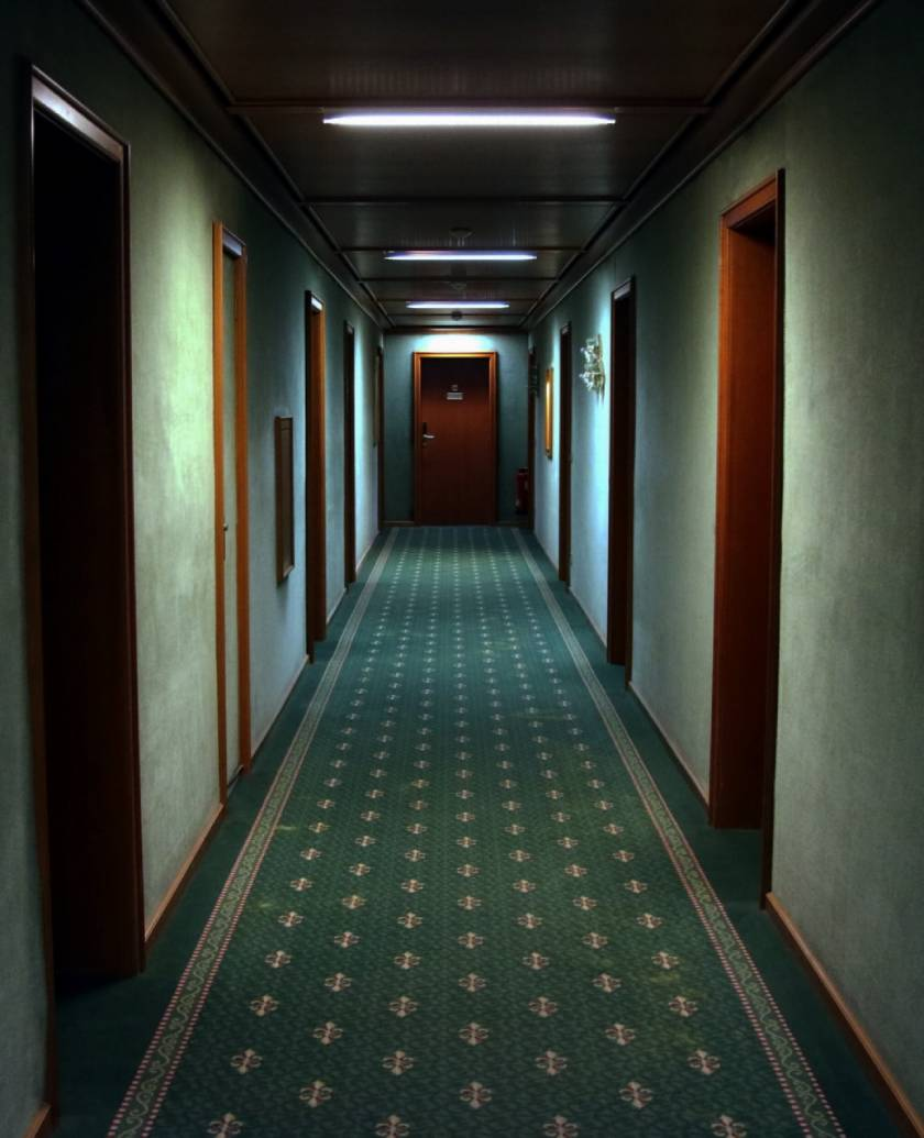 Dark, spooky hallway in a hotel with low lights and wooden doors lining each side