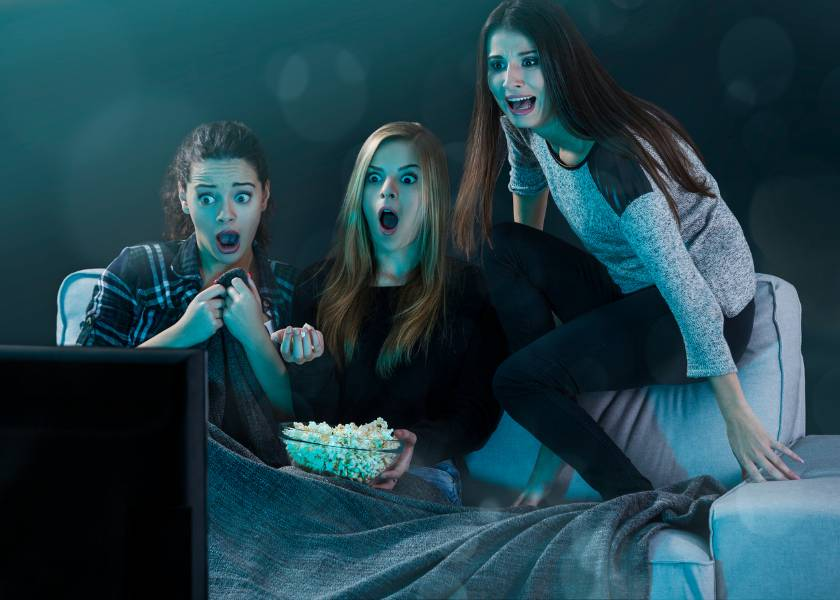 Three girls watching a horror movie at home with popcorn and getting scared