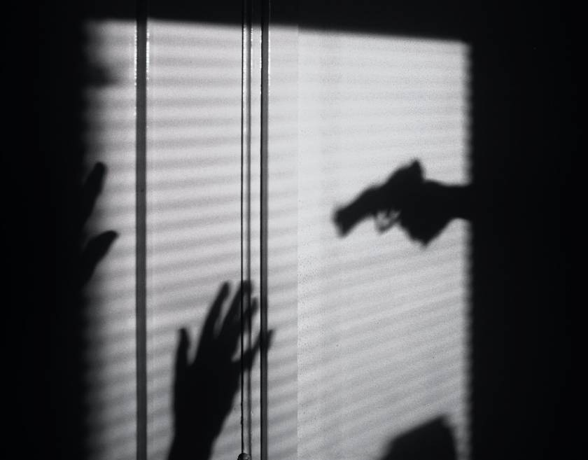 Shadow of a gun and a person holding up their hands - murder mystery film noire style