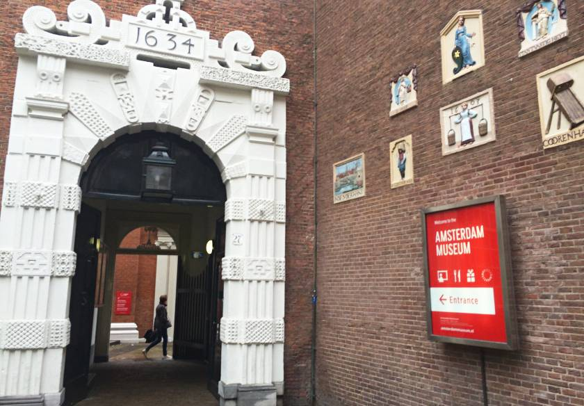 17th century white arch leading to the entrance of the Amsterdam Museum in Amsterdam with a sign on the wall for the museum